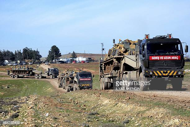 Turkish Army vehicles and tanks wait near the Syrian border in Suruc on February 23 2015 as almost 600 Turkish troops pushed deep into Syria in an...