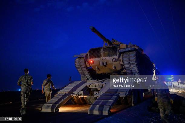 Turkish army's tank drives down from a truck as Turkish armed forces drive towards the border with Syria near Akcakale in Sanliurfa province on...