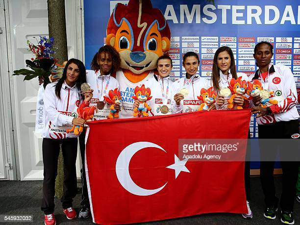 Turkish athletes pose after they won the bronze medal in the Women's Half Marathon Final on the last day of the European Athletics Championships in...
