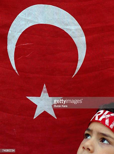 Turkish boy looks to his flag as tens of thousands of Turks attend an antigoverment rally May 5 2007 in western Turkish city of Manisa Tens of...