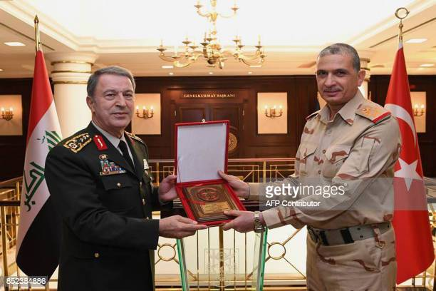 Turkish Chief of Staff General Hulusi Akar and his Iraqi counterpart General Othman Ali alGhanimi pose on September 23 2017 at the Turkish military...