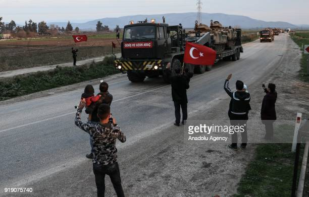 Turkish citizen waves a Turkish flag as Turkish Armed Forces' military vehicles are being transported to border units of Turkey's Reyhanli Kirikhan...