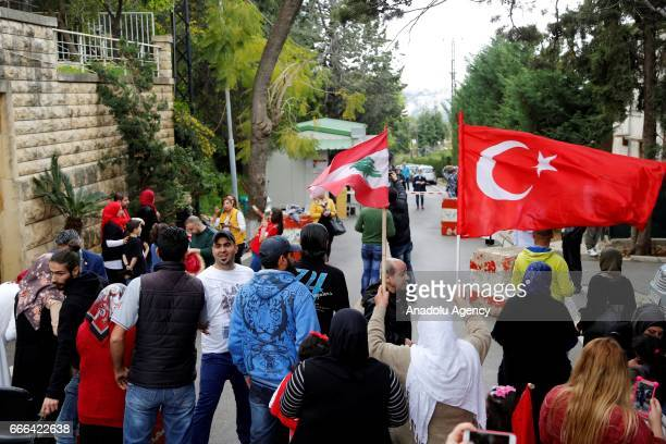 Turkish citizens arrive to cast their votes with Turkish flags prior to Turkey's upcoming constitutional referendum at Turkish Embassy in Beirut...