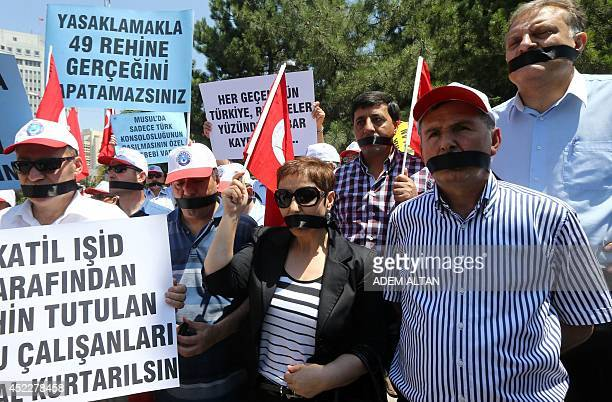 Turkish civil servants with black ribbons tied over their mouths stage a protest outside the Foreign Ministry in Ankara on July 17 2014 to demand the...