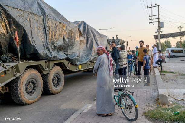 Turkish civilians look at a Turkish army's convoy driving towards the Syrian border near Akcakale in Sanliurfa province on October 9, 2019. - Turkey...