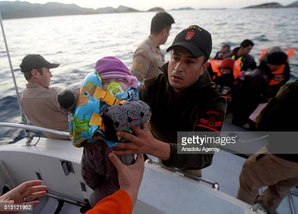 Turkish Coast guard member carries a baby into rescue boat after total of 174 Syrian refugees captured by Turkish coast guard while they were...