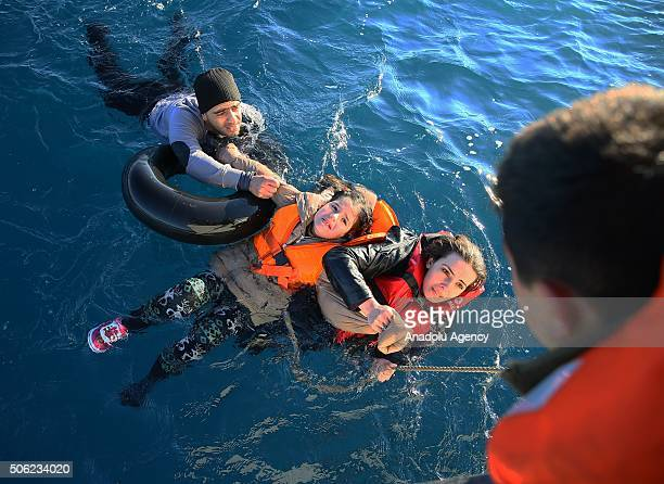 Turkish Coast Guard personnel help refugees as they swim with buoys after they toppled over a fishermen dinghy en route to Greece on January 22 2016...