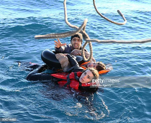 Turkish Coast Guard personnel throw a rope toward refugees as they swim with buoys after they toppled over a fishermen dinghy en route to Greece on...
