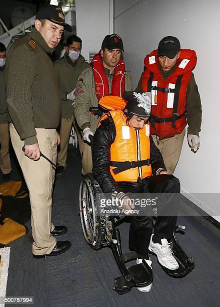 Turkish Coast Guard ship TCSG Umut crew members are seen with a wheel chair bound refugee man on December 10 2015 after refugees and asylum seekers...