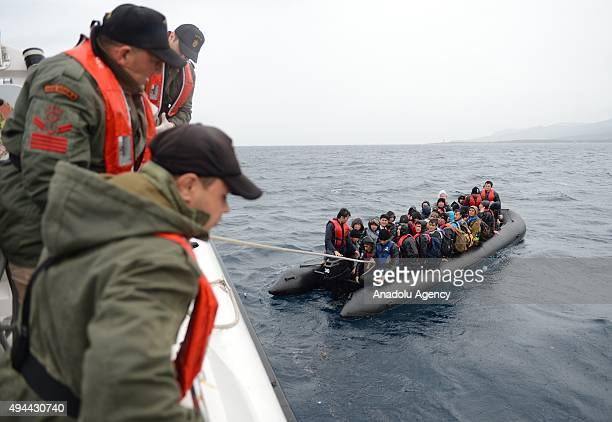 Turkish coast guards members are seen pulling a rope as they try to rescue refugees who were illegally trying to reach Greece's Lesbos island through...