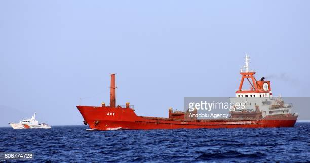 """Turkish commercial ship named """"ACT"""" is seen on Aegean coast of western Turkey's Mugla province on July 03, 2017 as a Turkish Coastal Guard boat..."""