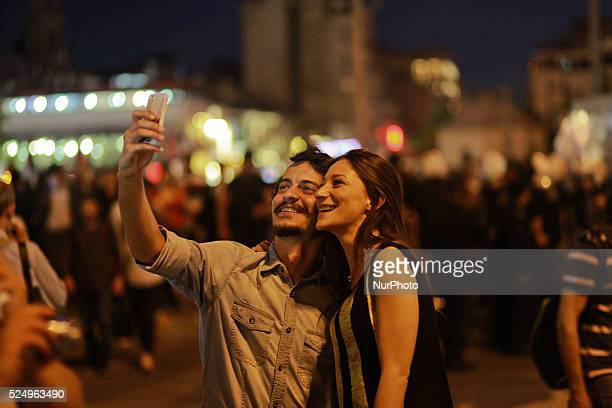 Turkish couple takes a photo of themselves with the Turkish policemen in background at Taksim square during a protest against the mining disaster in...