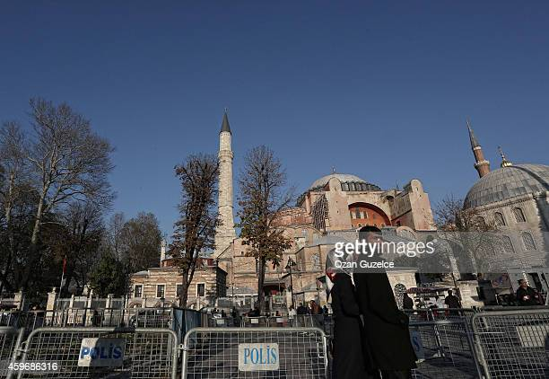 Turkish couple walks near the police security barricades in front of the sixth century Byzantine monument of Haghia Sophia before Pope Francis visit...