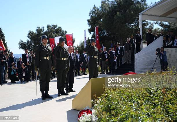Turkish Culture and Tourism Minister Nabi Avci lays stands in silence near martyrs' cemetery during the ceremony marking the 102nd anniversary of the...