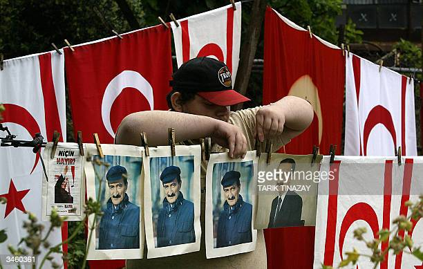 Turkish Cypriot boy hands pictures of former Turkish Prime Minister Bulent Ecevit who ordered the 1974 Turkish invasion of Cyprus and Turkish flags...