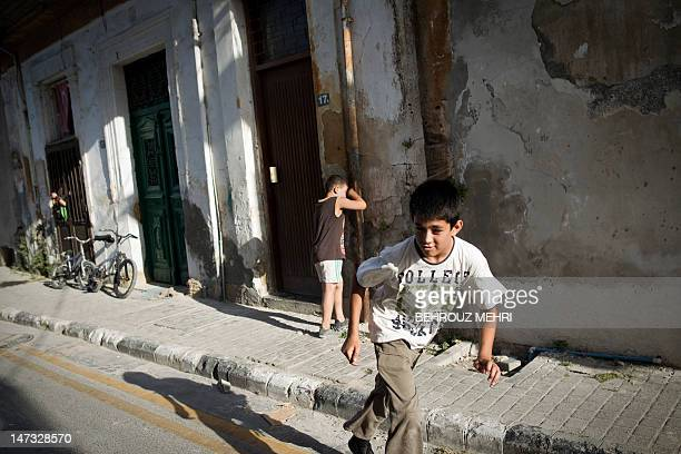 Turkish Cypriot boys play hide and seek at a street in the Turkishcontrolled northern side of Nicosia on June 25 2012 Nicosia has been divided by a...