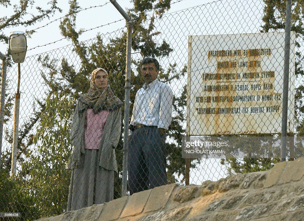 A Turkish Cypriot couple peer from behind a fence at the Green Line dividing the Cypriot capital Nicosia 25 April 2004, one day after Turkish Cypriots approved the UN plan to reunite while their Greek counterparts massively rejected it. Greek Cypriot leader Tassos Papadopoulos denied Sunday that he had deceived the international community by refusing to endorse a UN plan to reunify the island and alleged that the talks process had been riddled with flaws. Greek Cypriots in the internationally recognised south of the island voted overwhelmingly against the peace blueprint Saturday, killing efforts to unite the island in time for EU membership on May 1. AFP PHOTO/Nicholas KAMM AFP PHOTO/Nicholas KAMM