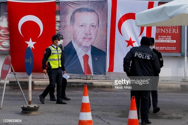 Turkish Cypriot police stand before portrait of Turkish President Recep Tayyip Erdogan on November 15, 2020 in the disputal coastal town of Varosha,...