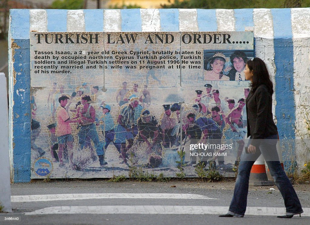 A Turkish Cypriot walks past an anti-Turkish mural on the Greek Cypriot side of the Green Line dividing the Cypriot capital Nicosia 25 April 2004, one day after Turkish Cypriots approved the UN plan to reunite while their Greek counterparts massively rejected it. Greek Cypriot leader Tassos Papadopoulos denied Sunday that he had deceived the international community by refusing to endorse a UN plan to reunify the island and alleged that the talks process had been riddled with flaws. Greek Cypriots in the internationally recognised south of the island voted overwhelmingly against the peace blueprint Saturday, killing efforts to unite the island in time for EU membership on May 1. AFP PHOTO/Nicholas KAMM