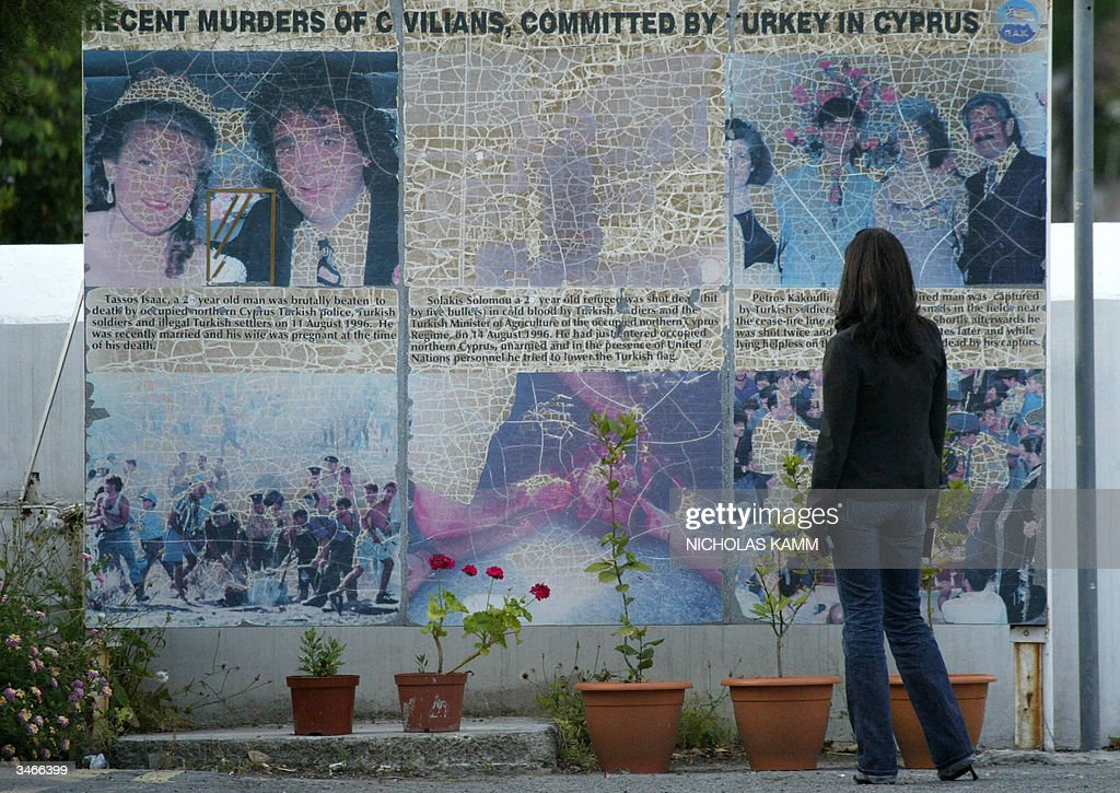 A Turkish Cypriot woman looks at anti-Turkish mural on the Greek Cypriot side of the Green Line dividing the Cypriot capital Nicosia 25 April 2004, one day after Turkish Cypriots approved the UN plan to reunite while their Greek couterparts massively rejected it. Greek Cypriot leader Tassos Papadopoulos denied Sunday that he had deceived the international community by refusing to endorse a UN plan to reunify the island and alleged that the talks process had been riddled with flaws. AFP PHOTO/Nicholas KAMM