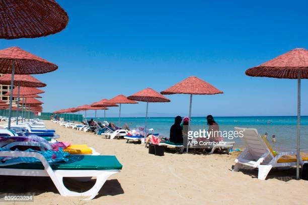 Turkish Cypriots sit at Derinya beach, close to the fenced-off touristic area of Varosha, in the eastern port city of Famagusta in the...