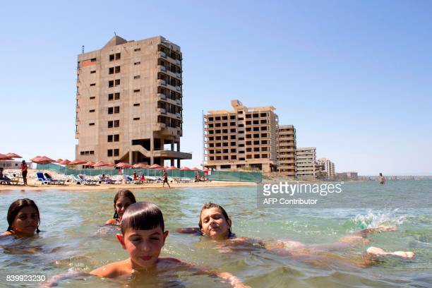 Turkish Cypriots take a dip at Derinya beach, close to the fenced-off touristic area of Varosha, in the eastern port city of Famagusta in the...