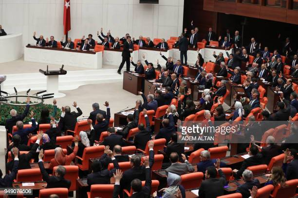 Turkish deputies take part in a vote for the proposed early presidential and parliamentary elections during the general assembly of Grand National...