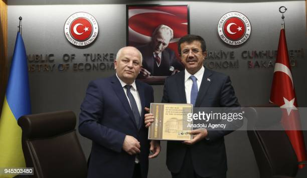 Turkish Economy Minister Nihat Zeybekci receives a book as a present from Ukraine's First Vice Prime Minister and Economy Minister Stepan Kubiv as...