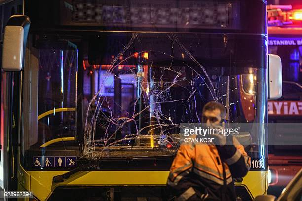 A Turkish emergency worker stand in front of a damaged bus on the site where a car bomb exploded near the stadium of football club Besiktas in...