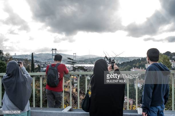 A Turkish family take photos of the the July 15 Martyrs' Bridge known as the Bosphorus Bridge during the 40th annual Istanbul Marathon on November 11...