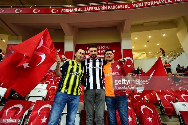 Turkish fans wearing Galatasaray Besiktas and Fenerbahce sport suits hold Turkish flags before the friendly football match between Turkey and Sweden...