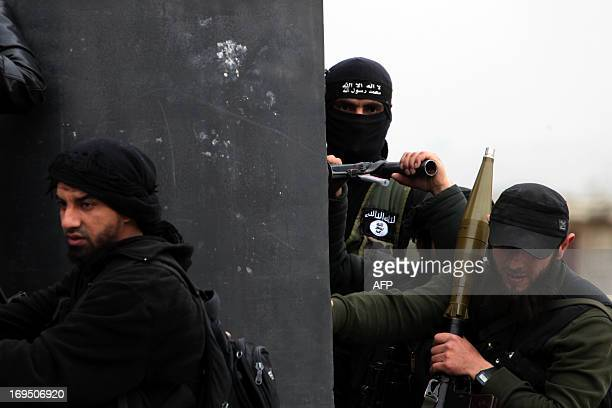 A Turkish fighter of the jihadist group AlNusra Front bearing the flag of AlQaeda on his jacket holds position with fellow comrades on April 4 2013...