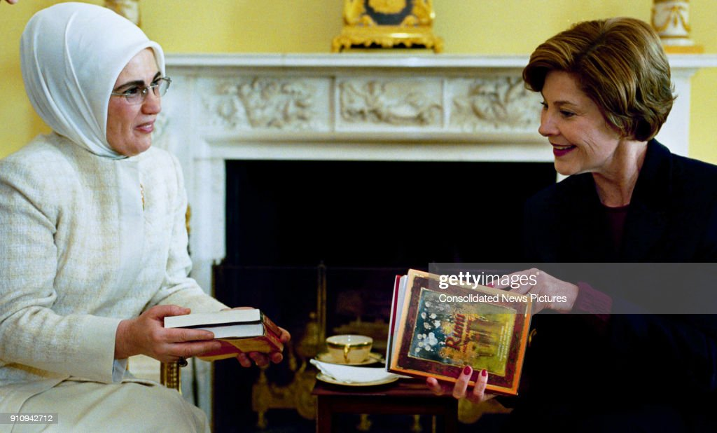 Turkish First Lady Emine Erdogan (left) presents US First Lady Laura Bush with a book (by Turkish poet Rumi) during a coffee meeting at the White House, Washington DC, January 29, 2004.
