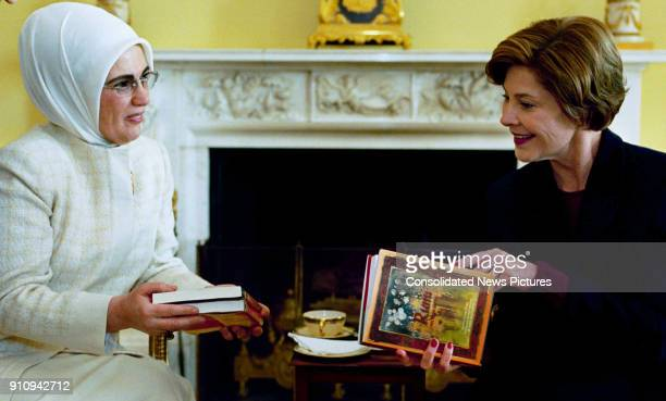 Turkish First Lady Emine Erdogan presents US First Lady Laura Bush with a book during a coffee meeting at the White House Washington DC January 29...