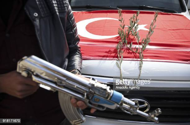 Turkish flag and an olive branch are seen in front of a convoy as people from Azez organized a convoy in support of 'Operation Olive Branch' launched...