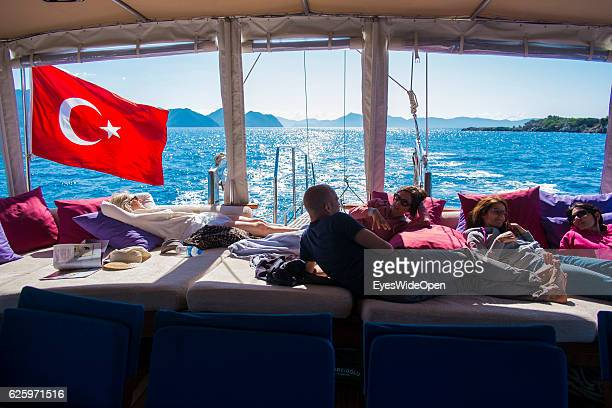 Turkish flag and people on a Yoga Cruise relax on the sailing boat a traditional Gulet at a Blue Voyage trip in the Aegean Sea on May 25 2014 in the...