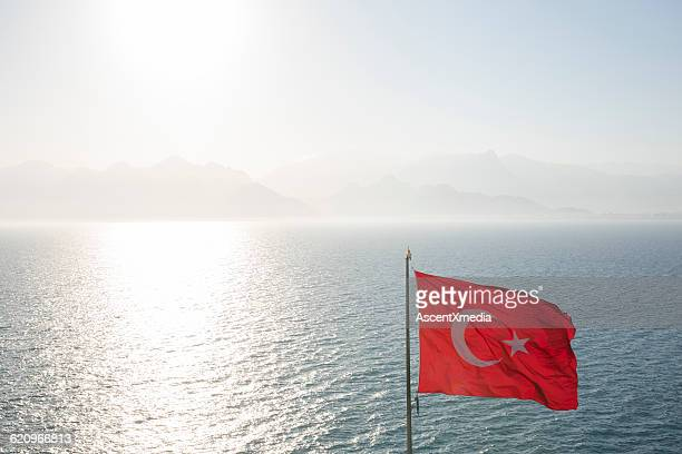 Turkish flag blows above sea, distant mountains