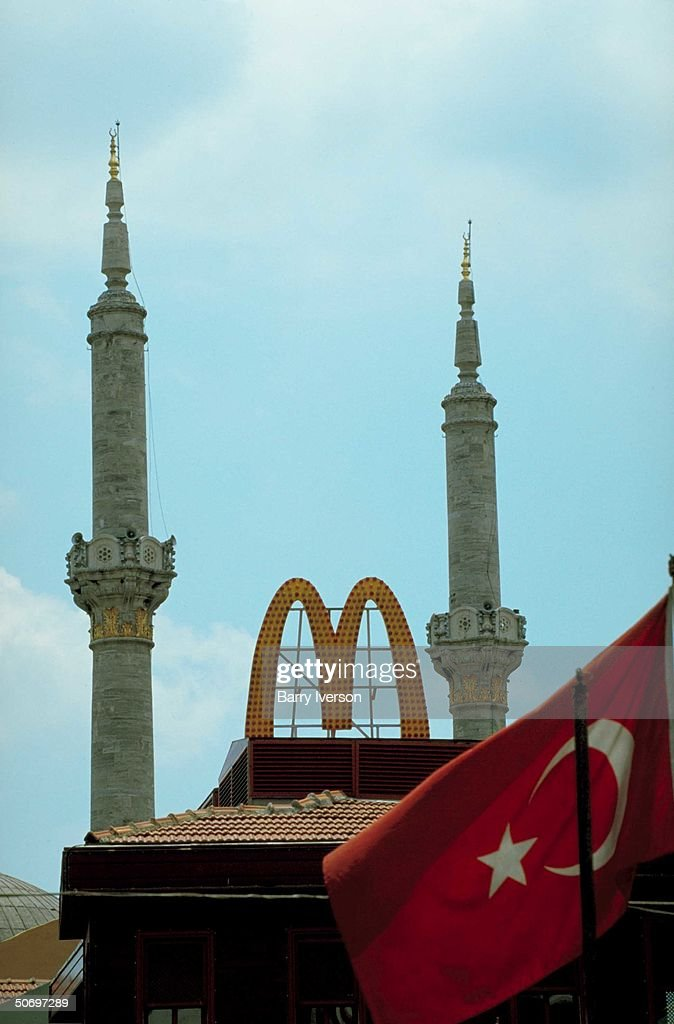 Turkish flag in front of mosque minarets framed by looming golden arches of American McDonald's fast food outlet in illustration of creeping Islamization of secular, pro-western oriented Turkish society.