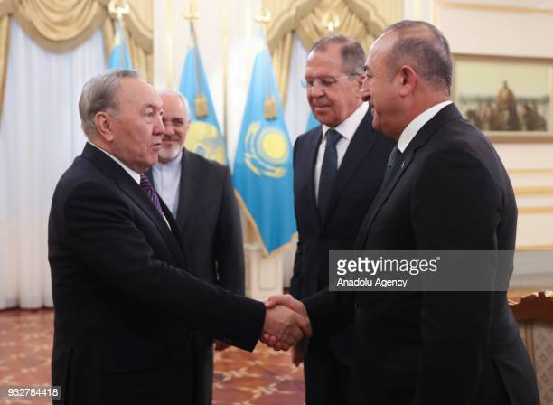 Turkish Foreign Affairs Minister Mevlut Cavusoglu shakes hands with President of Kazakhstan Nursultan Nazarbayev as they flanked by Russian Foreign...