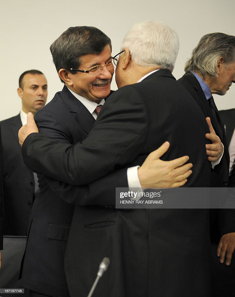 Turkish Foreign Minister Ahmet Davutoglu (L) hugs Palestinian President Mahmoud Abbas, prior to a meeting of the Committee on the Exercise of the Inalienable Rights of the Palestinian People, November 29, 2012 at UN headquarters in New York. AFP PHOTO/Henny Ray Abrams