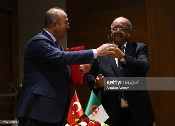 Turkish Foreign Minister Mevlut Cavusoglu and Algerian Foreign Minister Abdelkader Messahel exchange pens during agreement signing ceremony with the...