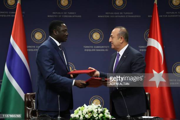 Turkish Foreign Minister Mevlut Cavusoglu and his Gambian counterpart Mamadou Tangara exchange folders during a bilateral agreements signing ceremony...