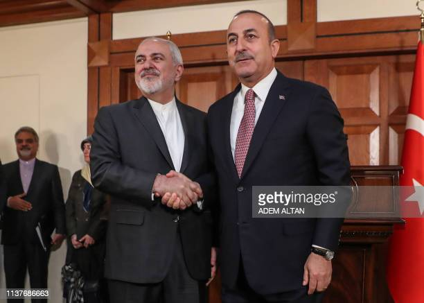 Turkish Foreign Minister Mevlut Cavusoglu and Iranian Foreign Minister Mohammad Javad Zarif shake hands after giving a press conference in Ankara...