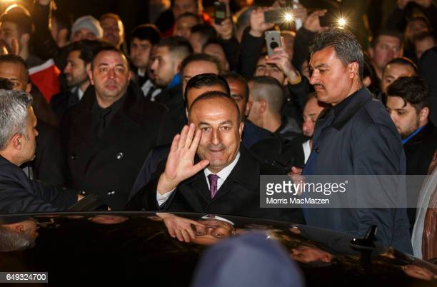 Turkish Foreign Minister Mevlut Cavusoglu emerges from the Turkish consulate after speaking to supporters of the upcoming referendum in Turkey on...