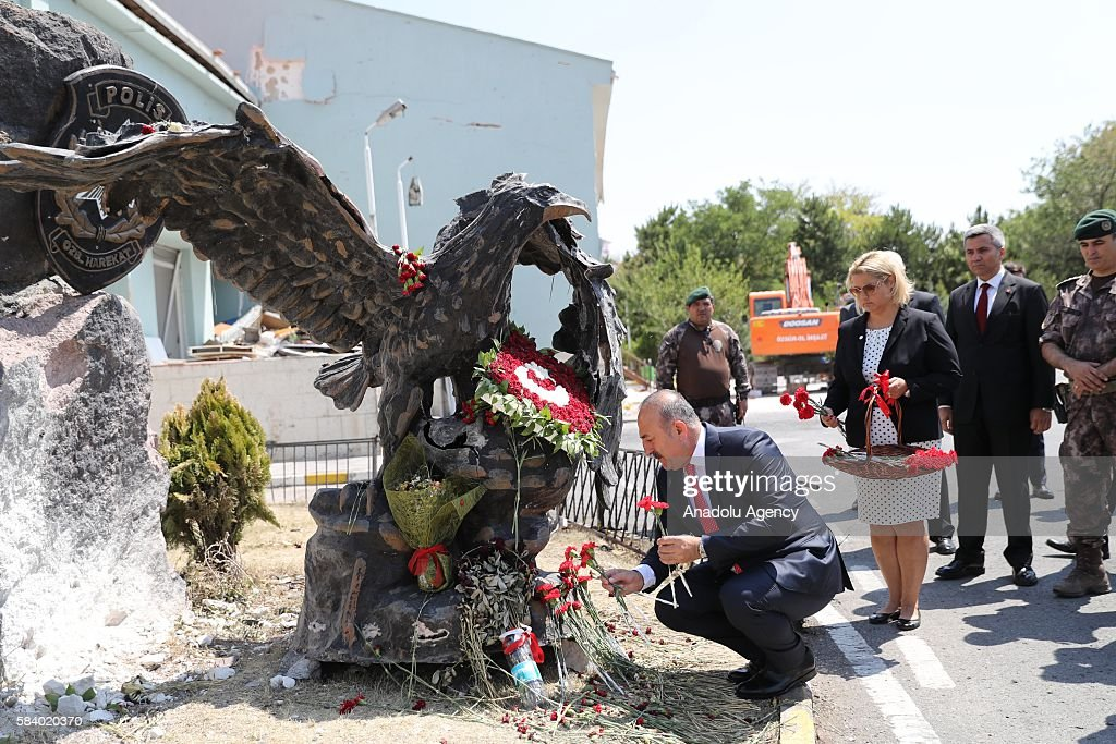 Turkish Foreign Minister Mevlut Cavusoglu (L) leaves red flowers at Police Special Operation Department's Headquarters in Golbasi district of Ankara, Turkey on July 28, 2016 after the Parallel State/Gulenist Terrorist Organization's failed military coup attempt staged on 15th of July 2016.