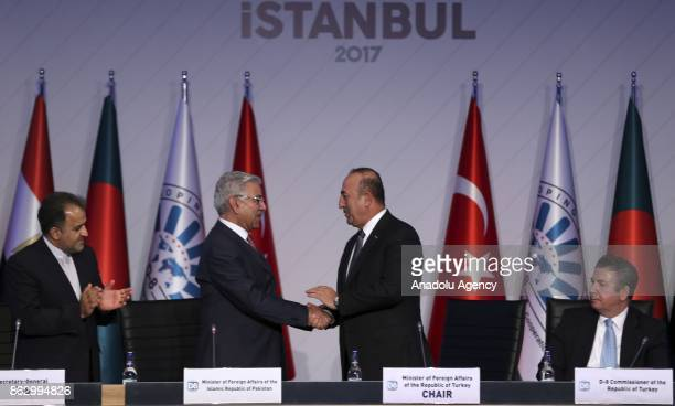 Turkish Foreign Minister Mevlut Cavusoglu shake hands after taking over the term presidency of summit from Pakistani Foreign Minister Khawaja...