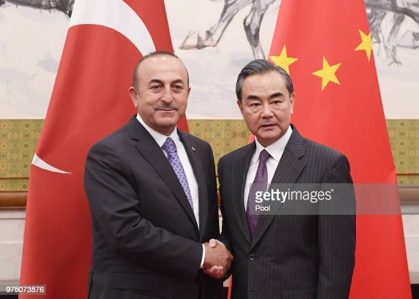 Turkish Foreign Minister Mevlut Cavusoglu shakes hands with Chinese Foreign Minister Wang Yi before a meeting on June 15 2018 in Beijing China