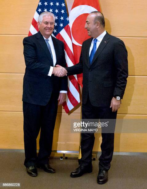 Turkish Foreign Minister Mevlut Cavusoglu shakes hands with US Secretary of State Rex Tillerson before a bilateral meeting on the sidelines of a NATO...