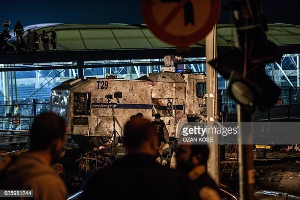 Turkish forensic police officers work next to bodies front of a water cannon vehicle on the site where a car bomb exploded near the stadium of...