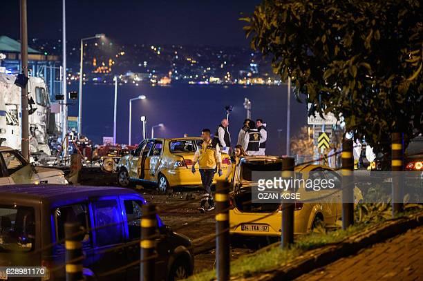 Turkish forensic police officers work next to damaged cars and police vehicles on the site where a car bomb exploded near the stadium of football...